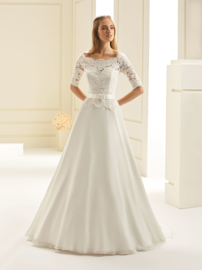 A beautiful lace and chiffon off-the-shoulder design with a-line skirt decorated with a satin belt and decorative bow at the front.