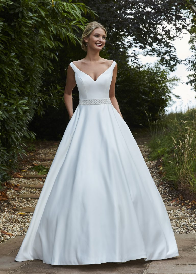 A sophisticated ballgown style, with a v neckline, hand beaded wide belt, pockets, buttons to the hem and finished with a v back with an illusion, hand beaded trim.