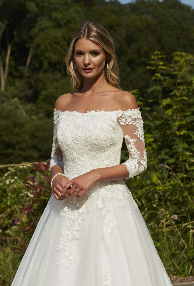 A sophisticated ballgown style with an off the shoulder neckline, illusion lace three quarter length sleeves, a lace bodice, cascading lace motifs and finished with a full tulle skirt.